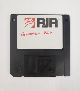 "A black 3.5 inch floppy disk with a label reading ""RJA: Geomsn.zip"""