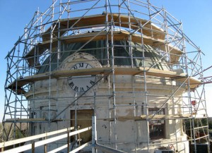 Scaffolding covers a green dome atop a white tower.