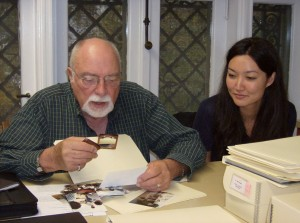Wayne Bell examines a photo more closely, with archives student Catherine Grady looking on