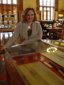 Katie Pierce stands by one the cabinets displaying drawings and artifacts from the Karl Kamrath Collection.